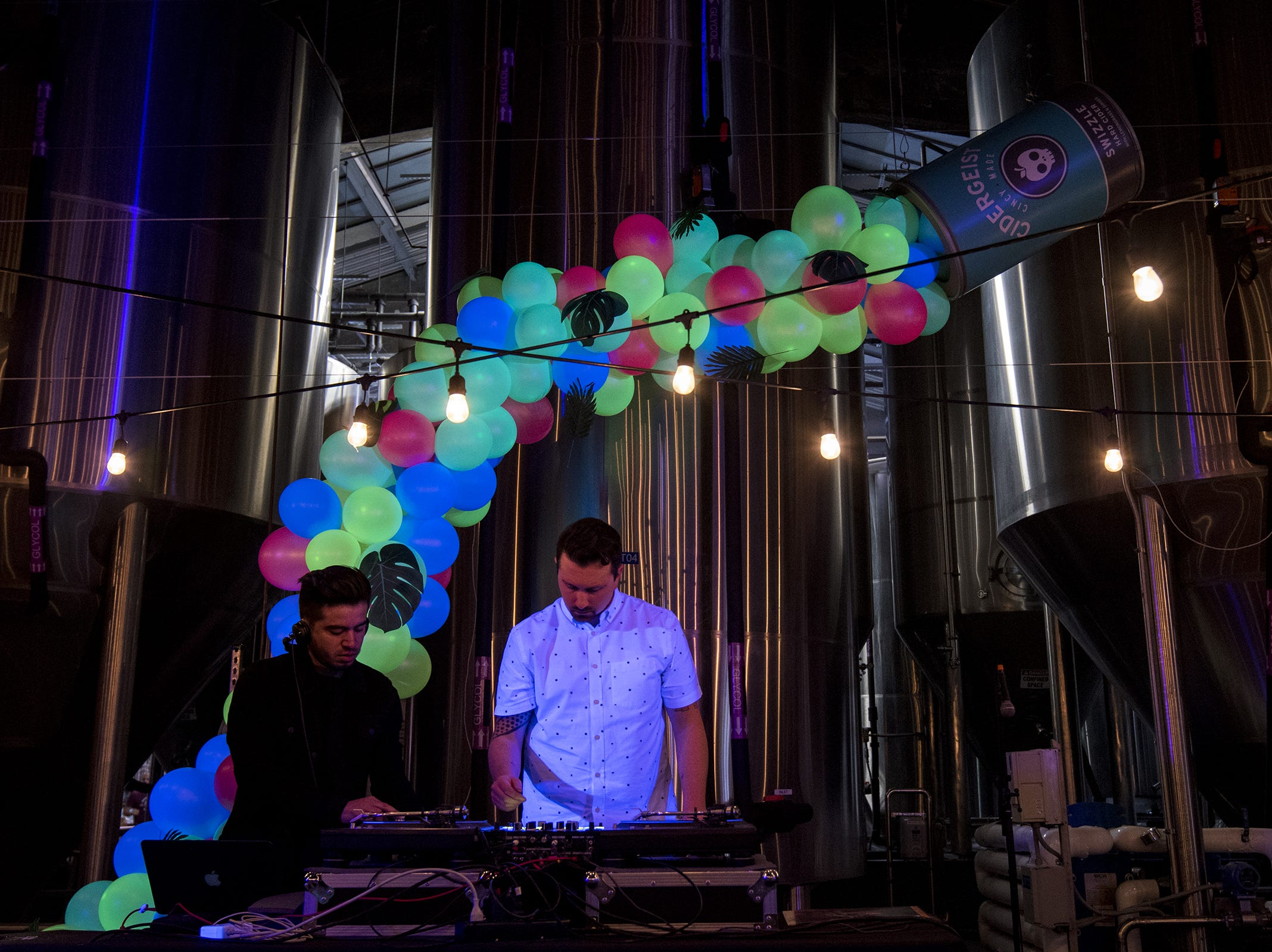 A giant Cidergeist Swizzle dumps balloons behind DJs Druski and Will Ross.