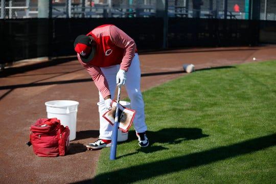 Cincinnati Reds right fielder Yasiel Puig (66) tars up a bat before batting practice at the Cincinnati Reds spring training facility in Goodyear, Ariz., on Saturday, Feb. 23, 2019.