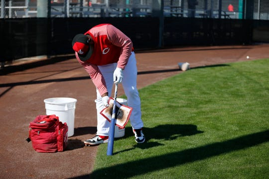 Cincinnati Reds right fielder Yasiel Puig (66) tars up a bat before batting practice at the Cincinnati Reds spring training facility in Goodyear, Ariz., on Saturday, Feb. 23, 2019.