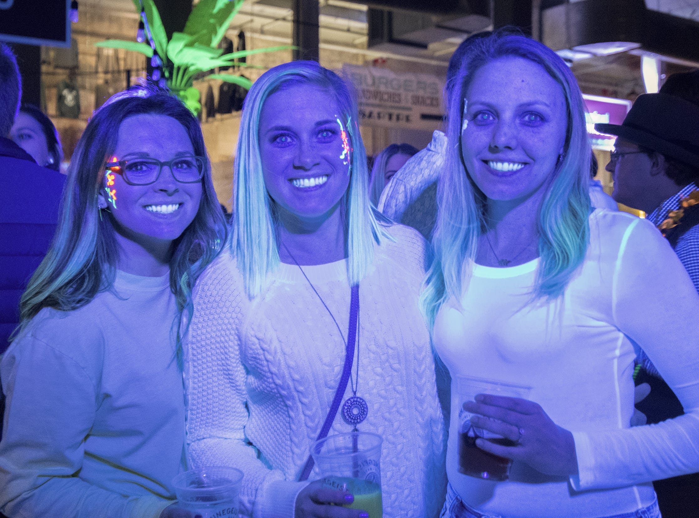 Hannah Ozment, Jordan Hauck and Dominique Thomas hang out under black lights after getting their faces painted.