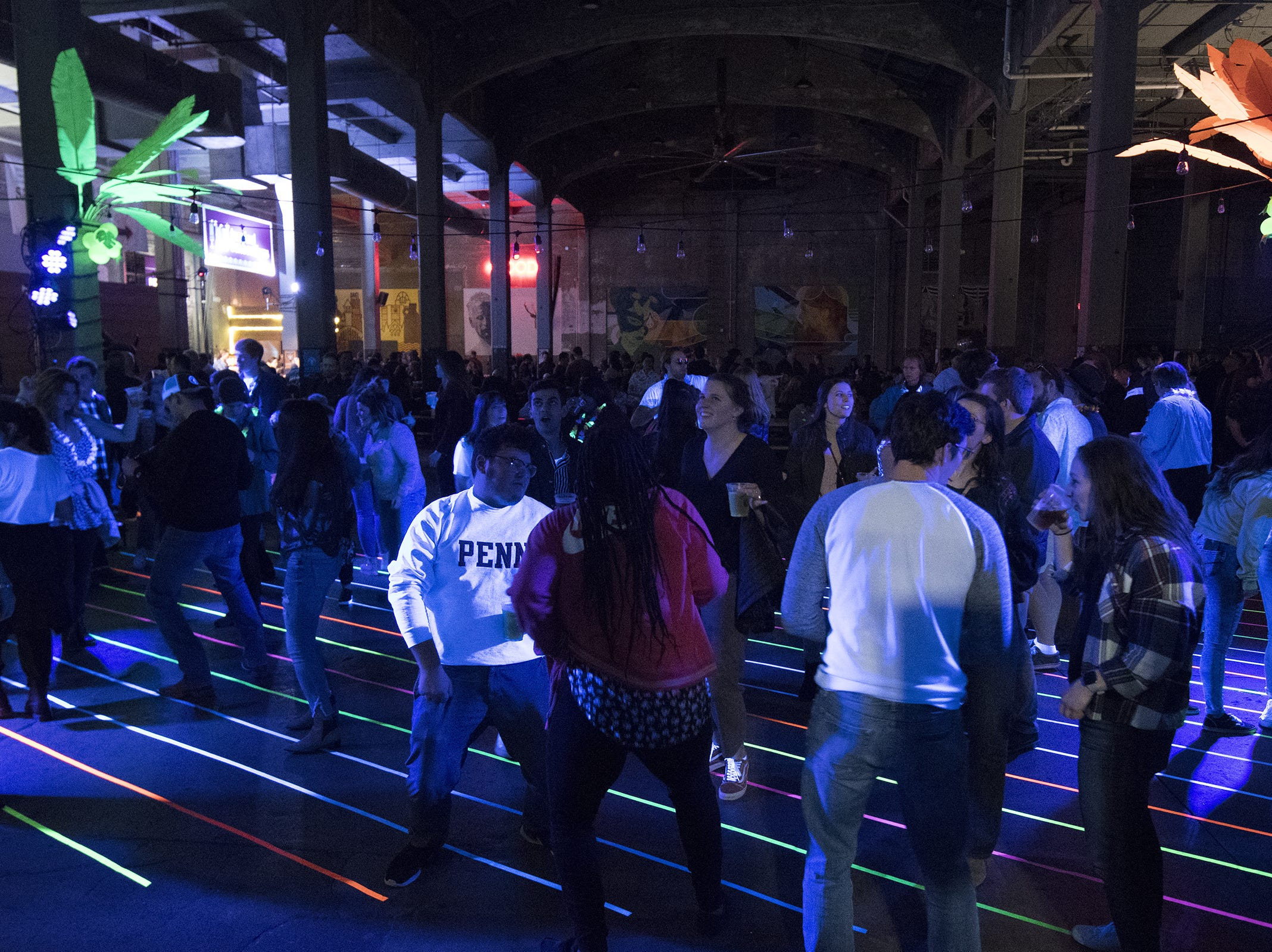 Guests boogie under black lights during a tropical disco at Rhinegeist.