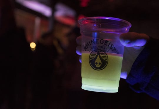 A black light shines up on a Rhinegeist beer during the tropical disco at Rhinegeist Friday, February 22, 2019 in Cincinnati, Ohio.