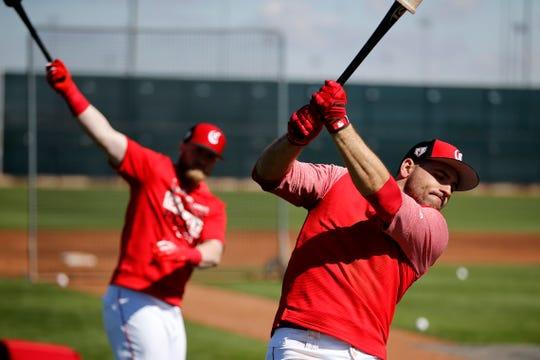 Cincinnati Reds catcher Tucker Barnhart (16) and first baseman Joey Votto (19) take slow swings before batting practice at the Cincinnati Reds spring training facility in Goodyear, Ariz., on Saturday, Feb. 23, 2019.