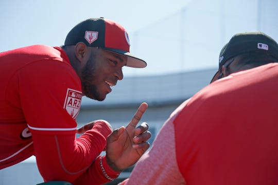 Cincinnati Reds right fielder Yasiel Puig (66) jokes outside the dugout before the first inning of the spring training opener between the Cleveland Indians and Cincinnati Reds at Goodyear Ballpark in Goodyear, Ariz., on Saturday, Feb. 23, 2019.
