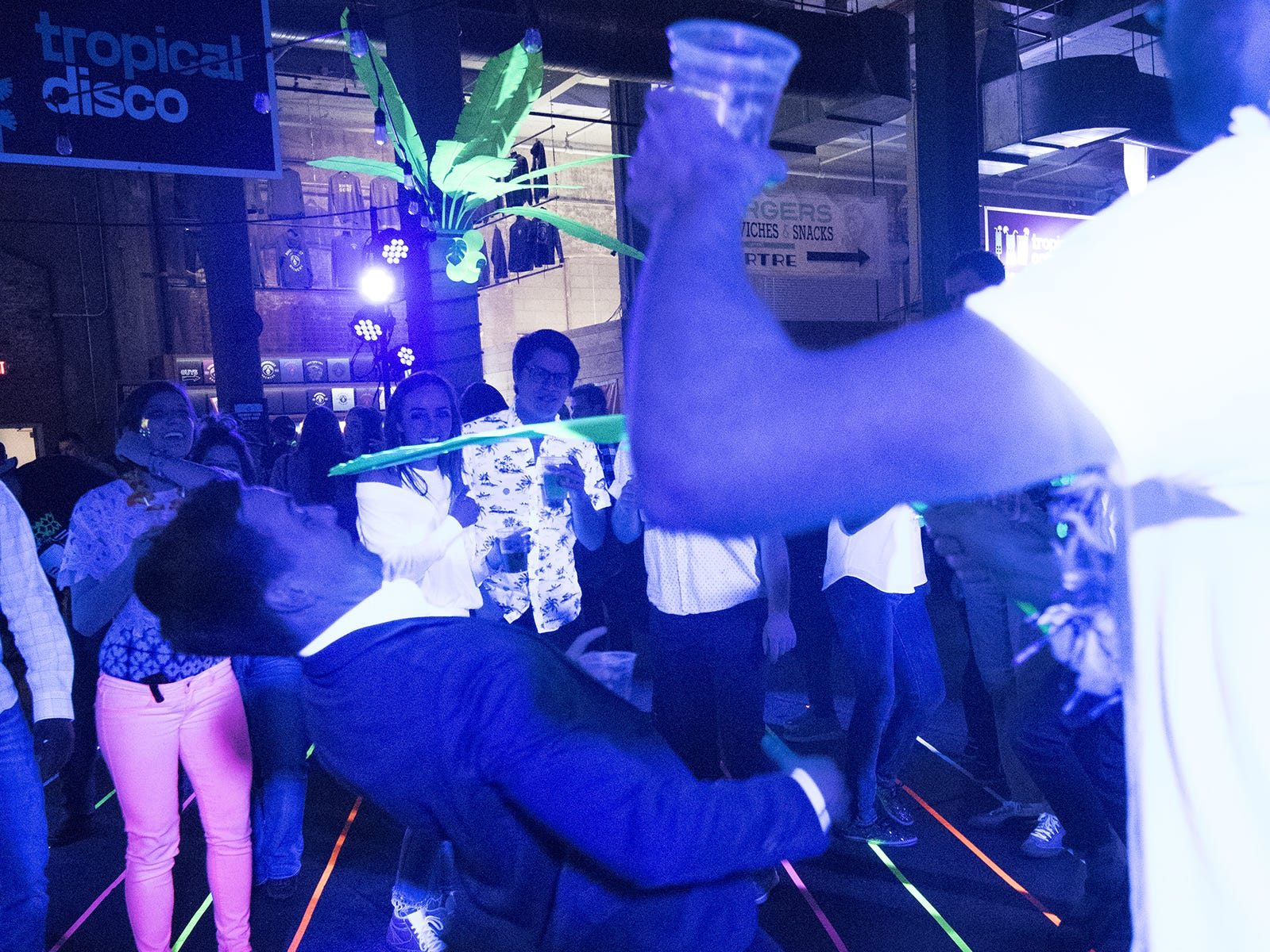 Guests play limbo on the dance floor during a tropical disco.