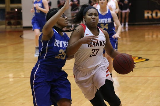 Rossview's Courtney Daniels (33) tries to drive past Wilson Central's Teoria Woods during the first half of their Region 5 tournament quarterfinal game Friday at Rossview High School.