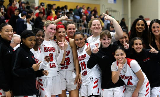 The Bishop Ahr girls basketball team celebrates its win over Edison in the GMC Tournament final on Friday, Feb. 22, 2019 at Middlesex County College.