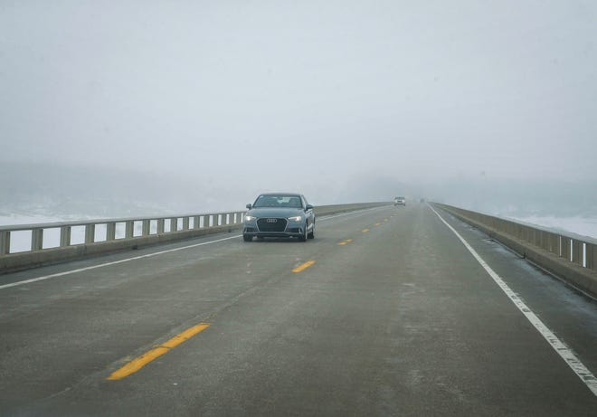 Vehicles cross the Saylorville Lake bridge as heavy fog creates visibility issues prior to another round of winter weather on Saturday, Feb. 23, 2019, in Polk City.