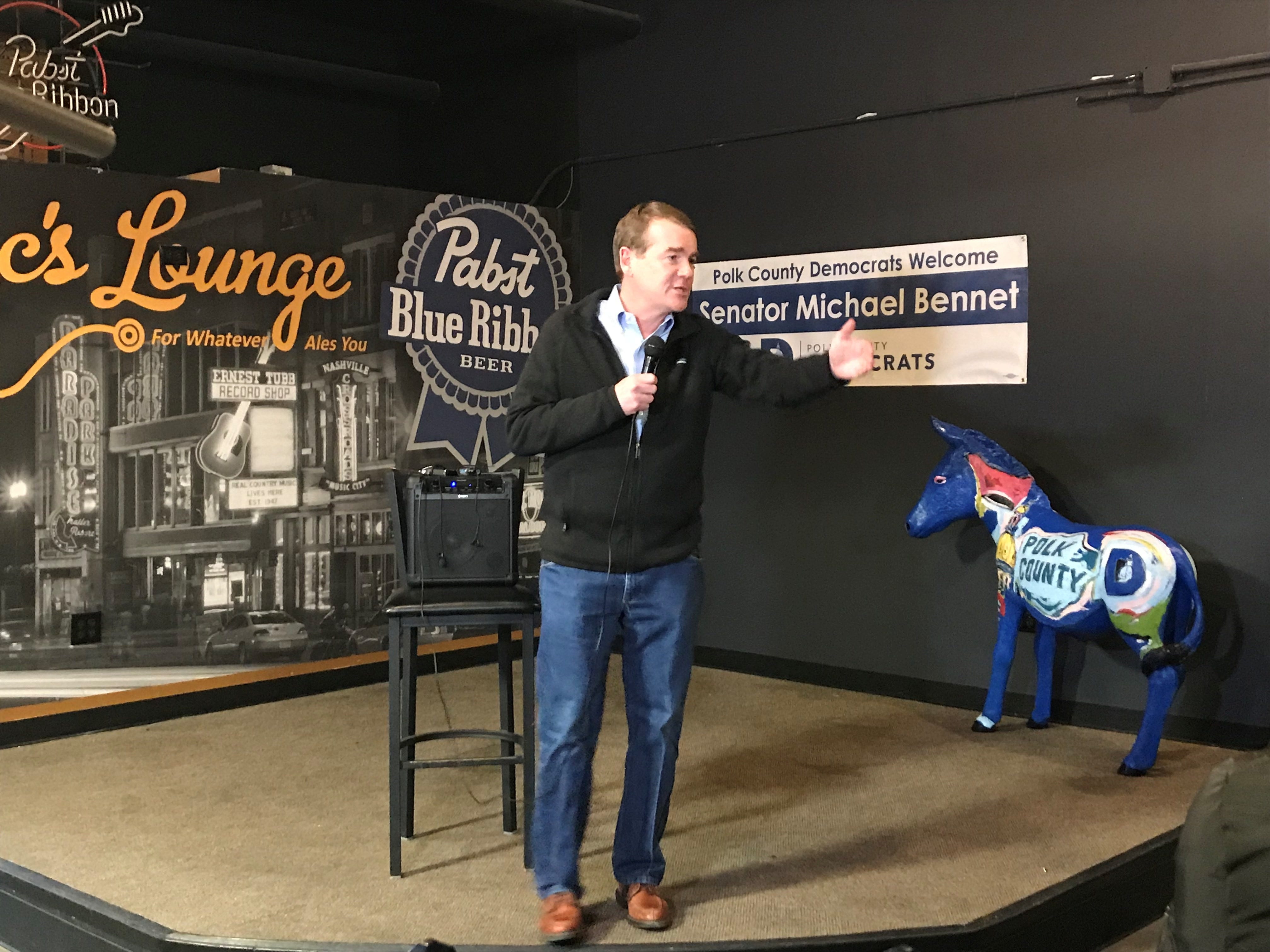 Sen. Michael Bennet, D-Colorado, answers questions from the crowd at Doc's Lounge in Johnston on Friday.