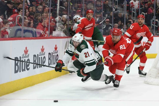 Detroit Red Wings defenseman Trevor Daley (83) and Minnesota Wild center Eric Fehr (21) battle for the puck during the first period at Little Caesars Arena on Feb. 22, 2019.