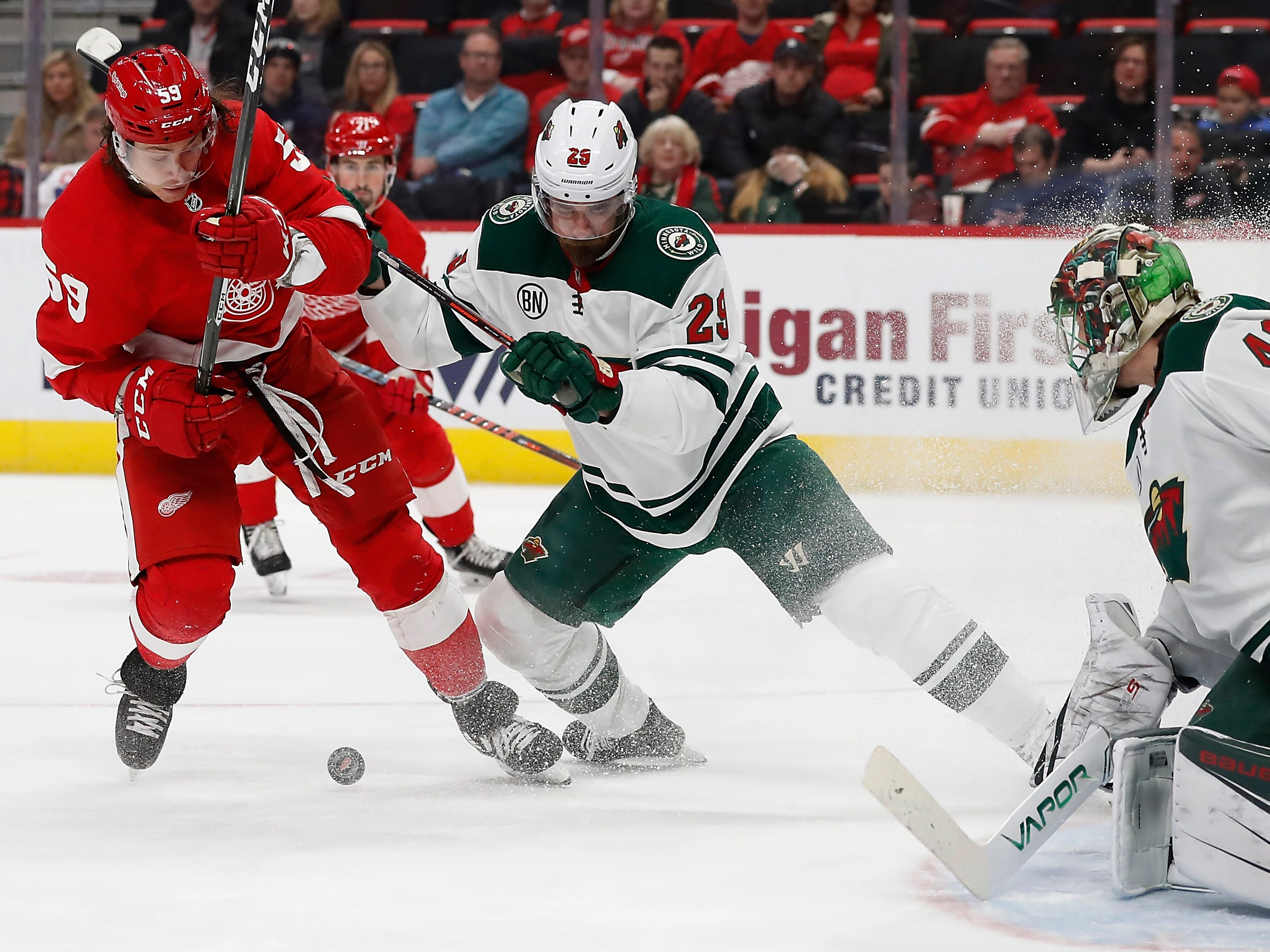 Minnesota Wild defenseman Greg Pateryn (29) checks Detroit Red Wings left wing Tyler Bertuzzi (59) in front of goaltender Devan Dubnyk (40) during the first period of an NHL hockey game Friday, Feb. 22, 2019, in Detroit.