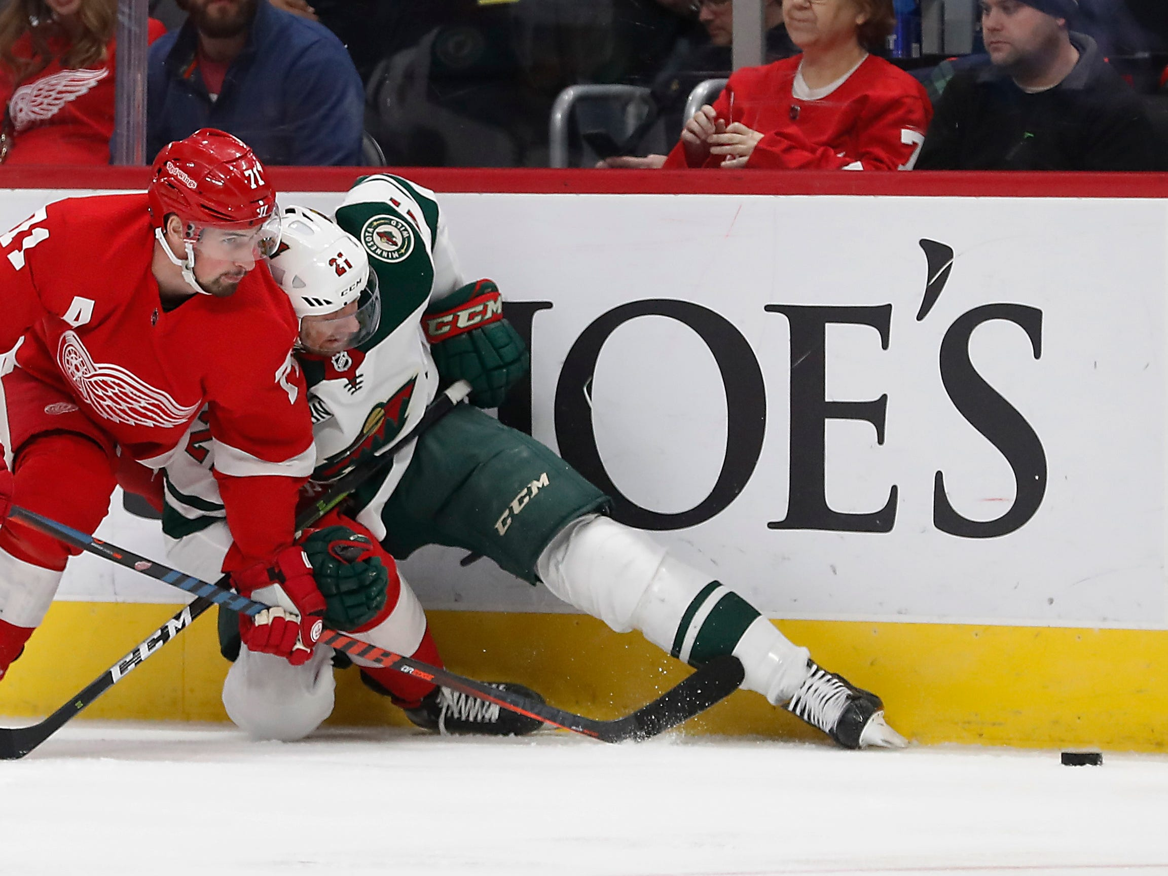 Detroit Red Wings center Dylan Larkin (71) checks Minnesota Wild center Eric Fehr (21) into the boards during the first period of an NHL hockey game Friday, Feb. 22, 2019, in Detroit.