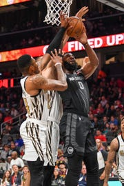 Detroit Pistons center Andre Drummond (0) is defended from the basket by Atlanta Hawks guard Kent Bazemore (24) and center Alex Len (25) during the first half at State Farm Arena on Feb. 22, 2019.