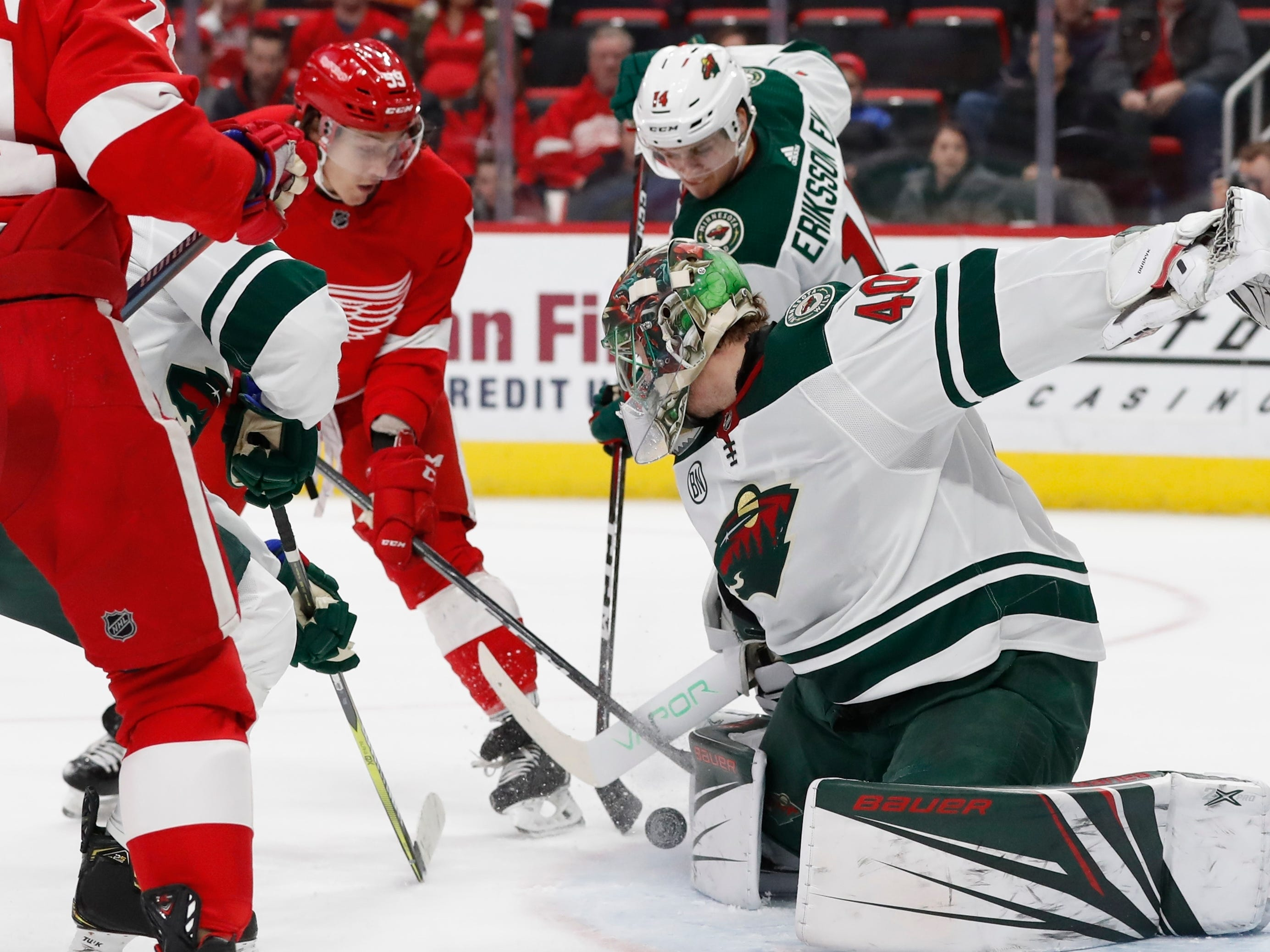 Minnesota Wild goaltender Devan Dubnyk (40) deflects a shot by Detroit Red Wings left wing Tyler Bertuzzi (59) during the first period of an NHL hockey game Friday, Feb. 22, 2019, in Detroit.
