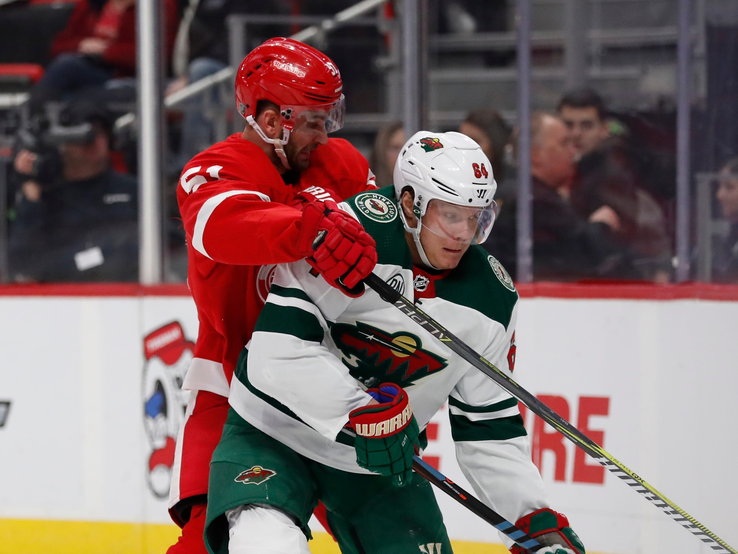 Detroit Red Wings center Frans Nielsen (51) checks Minnesota Wild right wing Mikael Granlund (64) during the second period of an NHL hockey game Friday, Feb. 22, 2019, in Detroit.