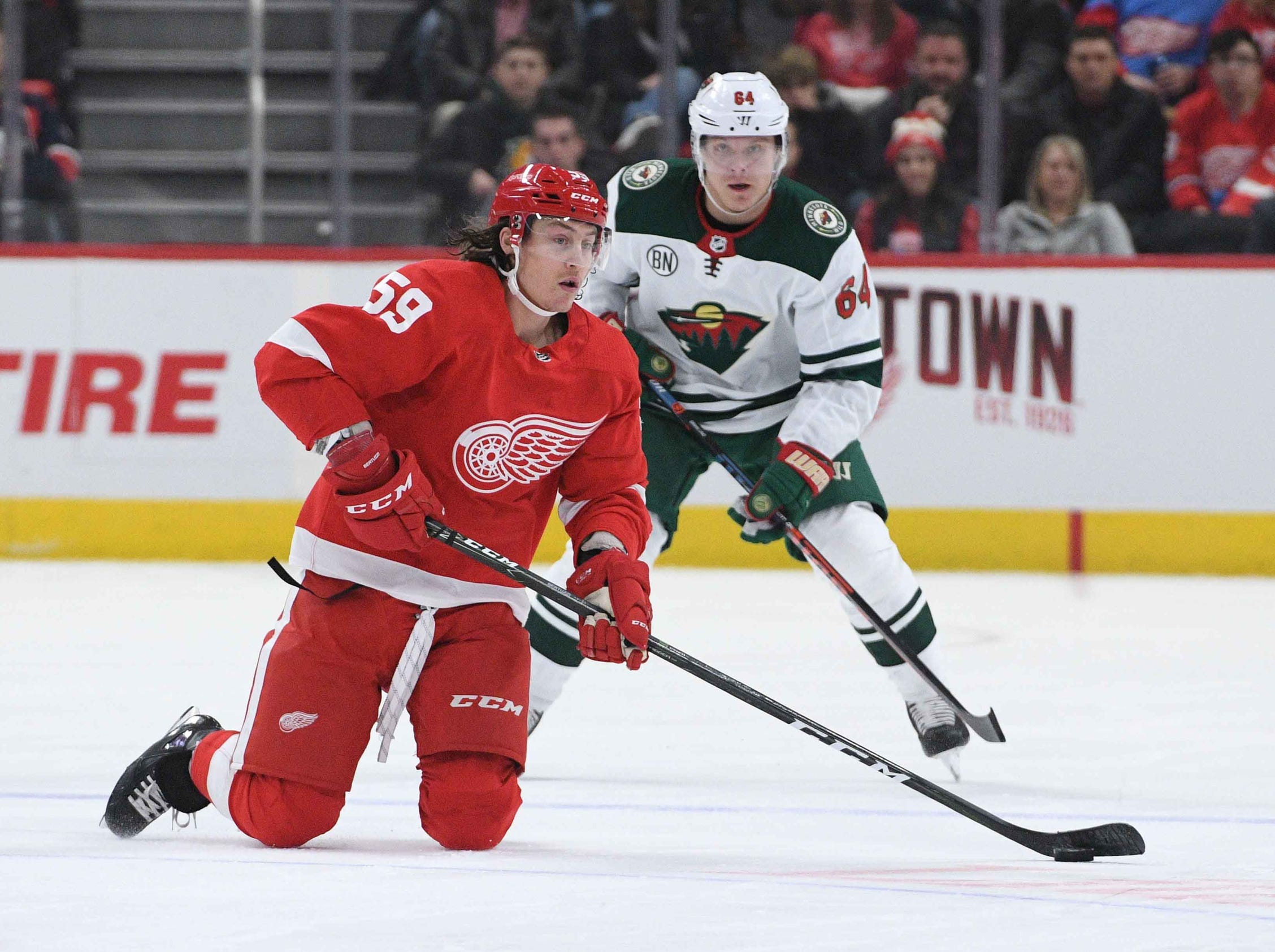 Detroit Red Wings left wing Tyler Bertuzzi (59) looks to pass the puck as Minnesota Wild right wing Mikael Granlund (64) defends during the first period at Little Caesars Arena on Feb. 22, 2019.