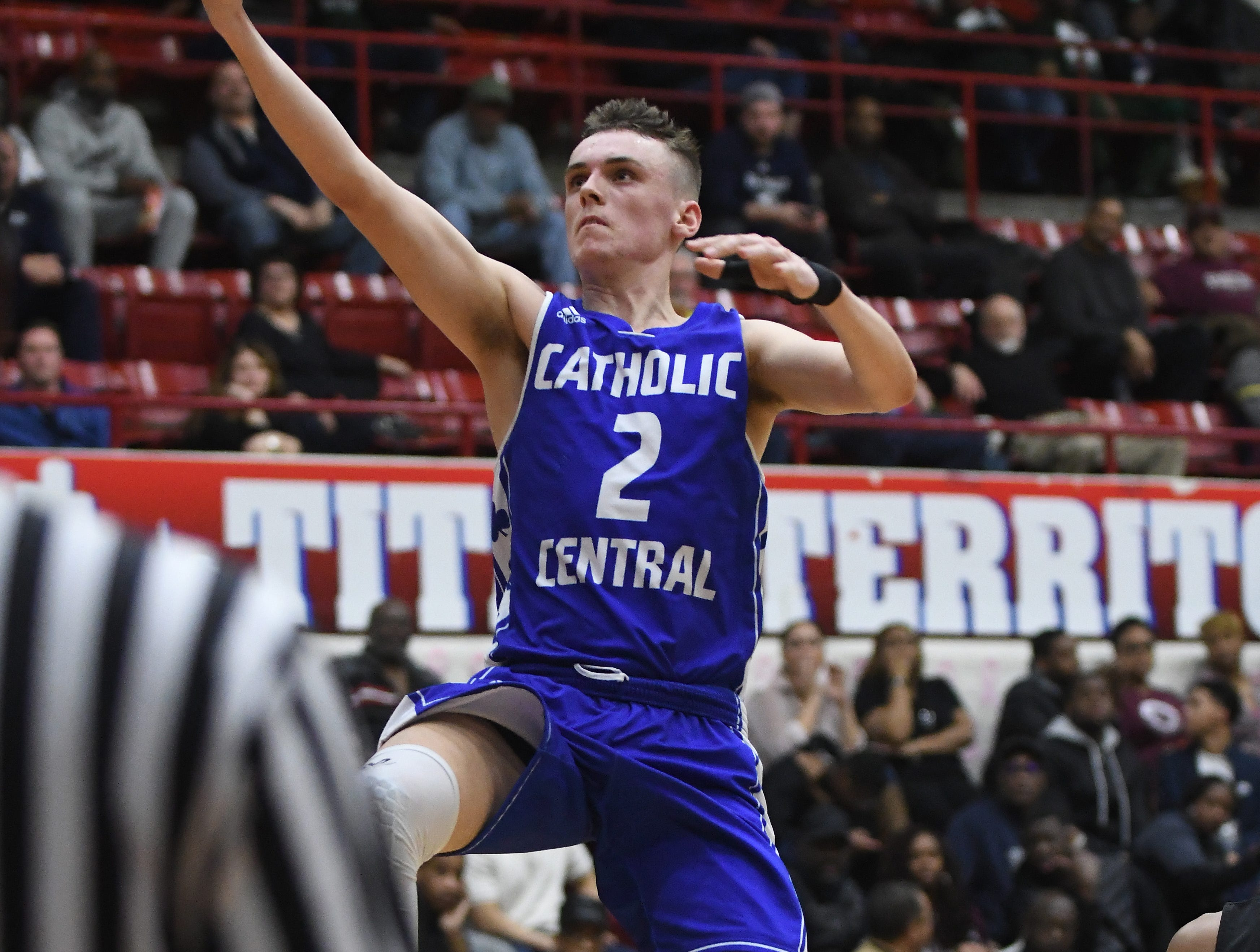 Catholic Central's Brendan Downs lays in two points late in the second half of the consolation game.