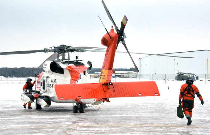 The U.S. Coast Guard's John Axelson, left, performs pre-flight checks as Brad Fitzpatrcik walks out to assist.