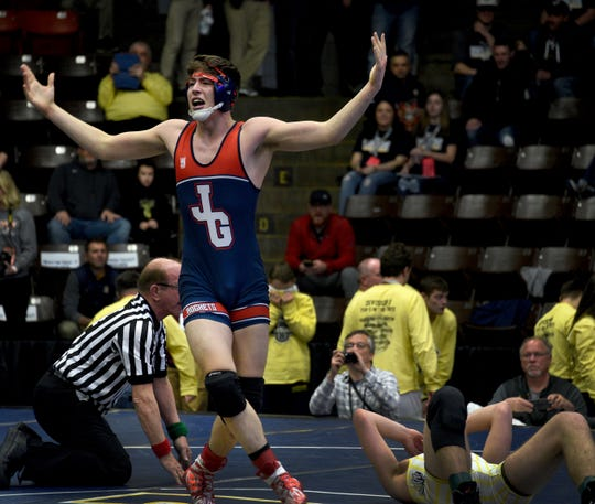 Hayden Rhoades of Westland John Glenn celebrates after he pinned Paul Corder of Hartland in the second period of a 189-pound match Friday.