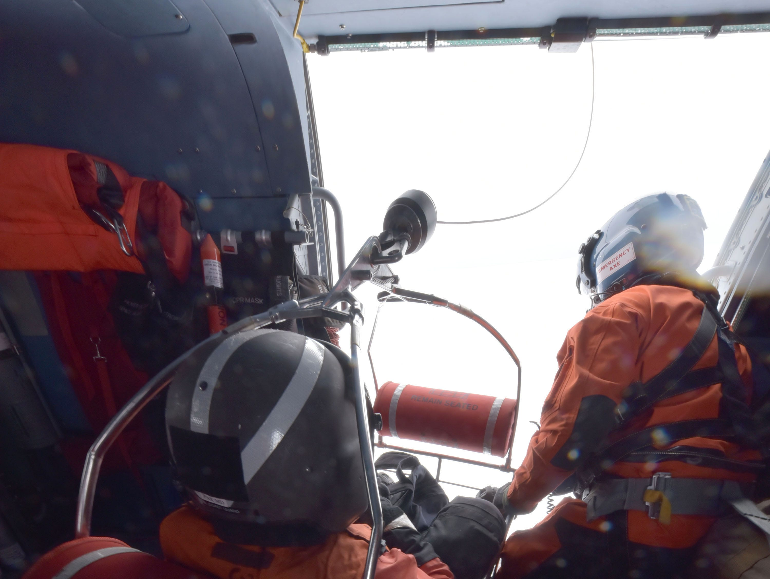 The U.S. Coast Guard John Axelson, right, prepares to lower a basket with Mike Godell to perform repair and maintenance work at the White Shoal Lighthouse in upper Lake Michigan Thursday, Feb. 14, 2019. Two Coast Guardsmen were lowered 130 feet to the ice-encrusted light from an MH-60T Jayhawk helicopter to the 109-year-old light's beacon, which is automated.