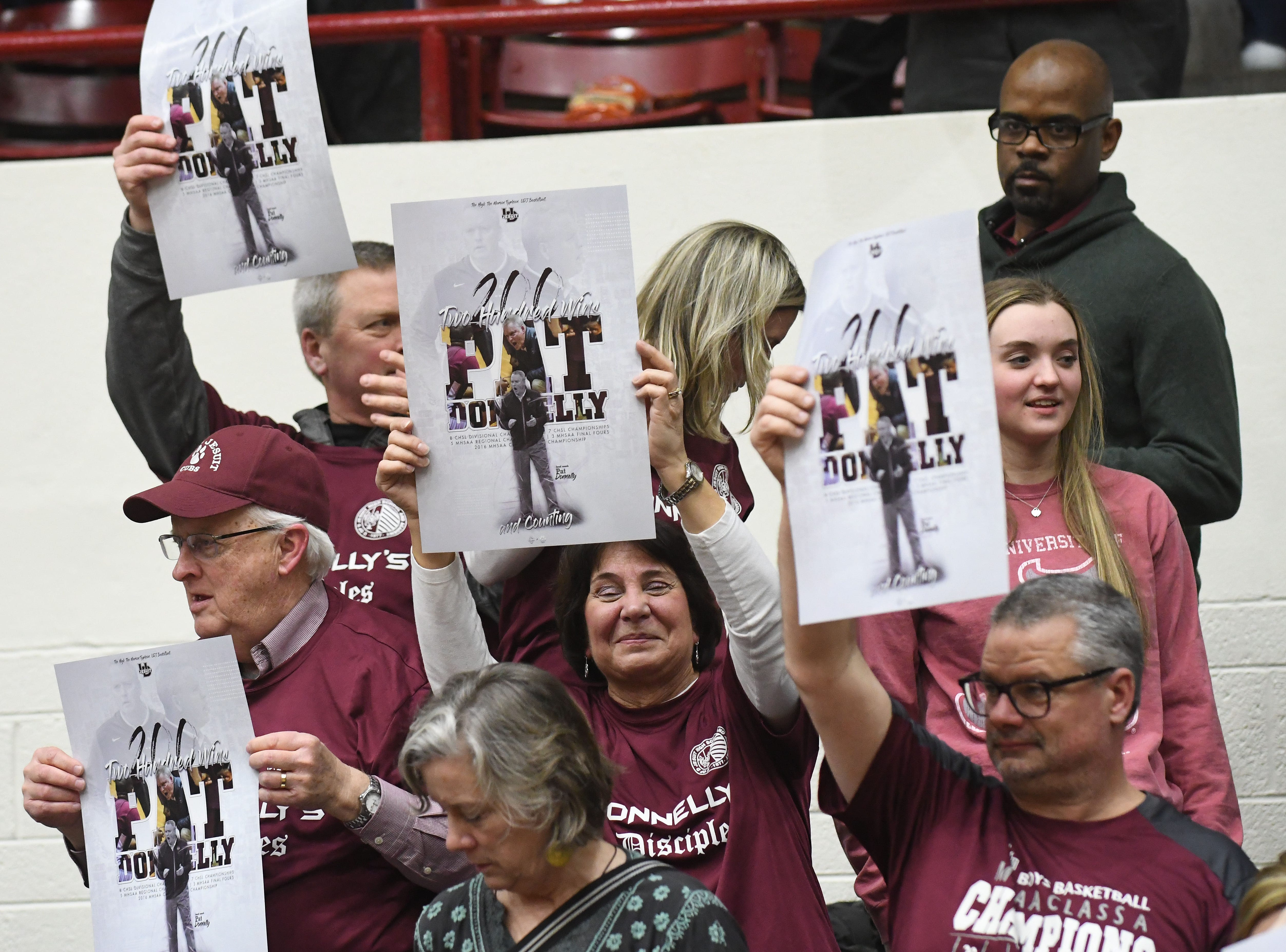 U of D Jesuit fans and family hold up signs stating the 79-59 victory over Cass Tech is coach Pat Donnelly's 200 win.