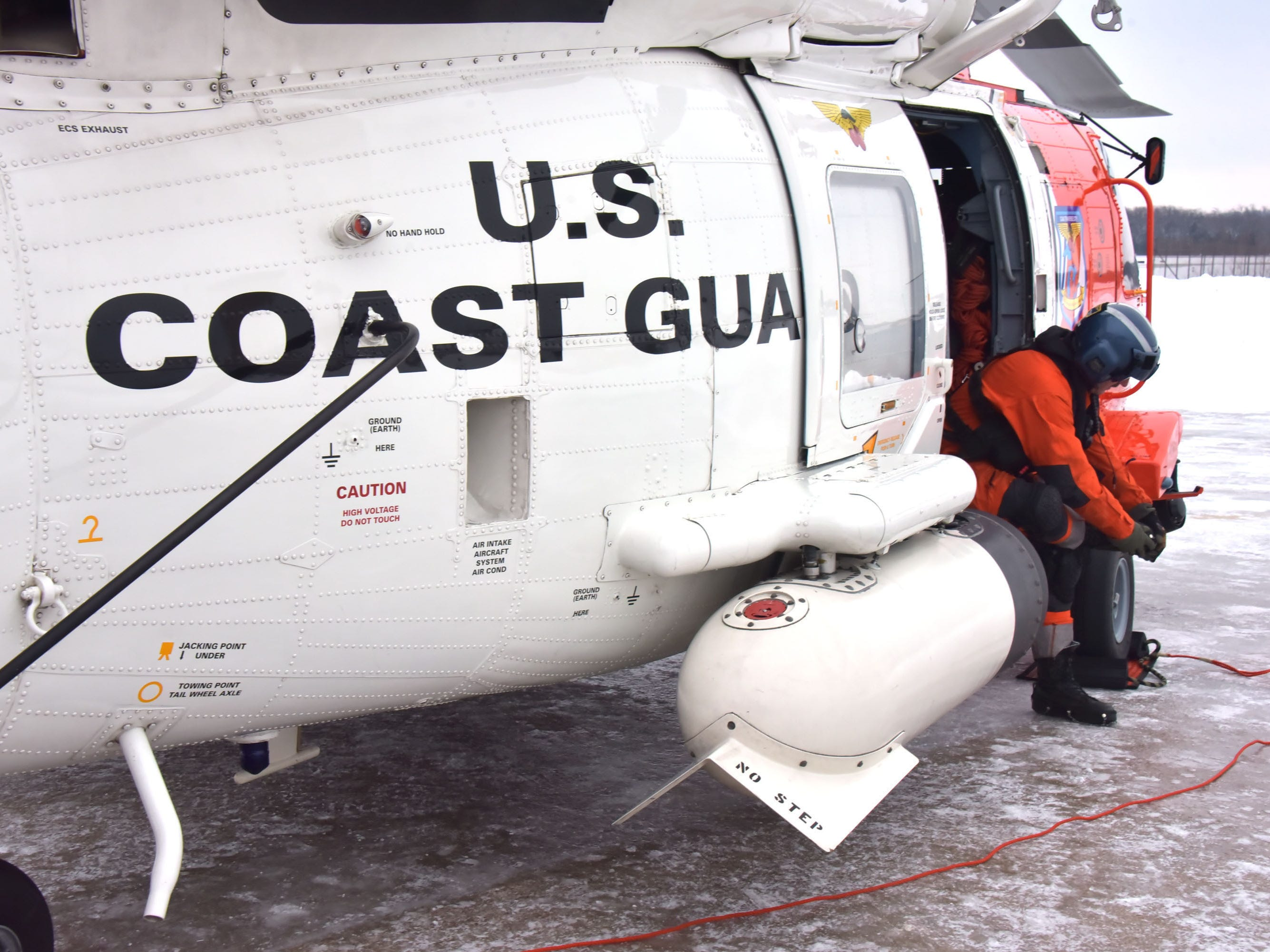 U.S. Coast Guard Air Station Traverse City's John Axelson pulls on ice cleats prior to an Aids to Navigation flight.