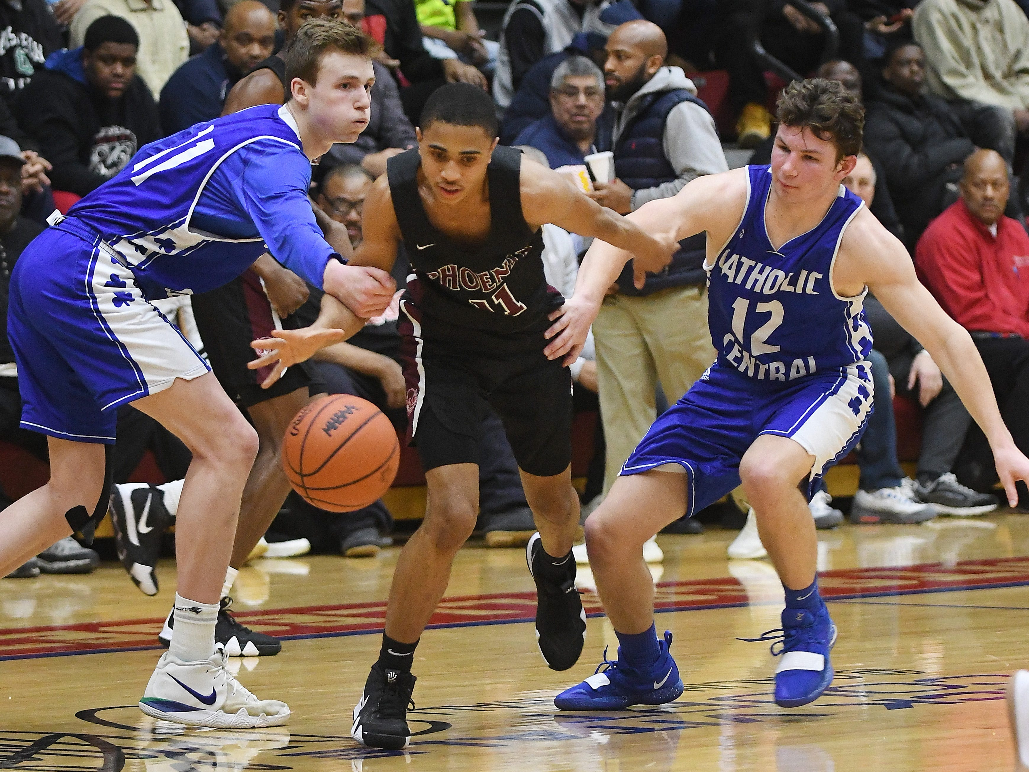 Renaissance's Juwan Maxey is fouled by Catholic Central's Justin Rukat late in the game with teammate Keegan Koehler defending in the second half of the consolation game.