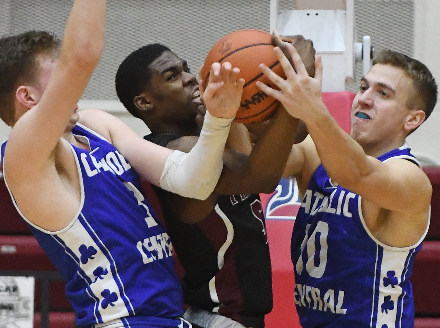 Renaissance's Kaylein Marzetter, center, fights for a rebound against Catholic Central's Davis Lukomski and Mike Harding under the basket in the first half of the consolation game.