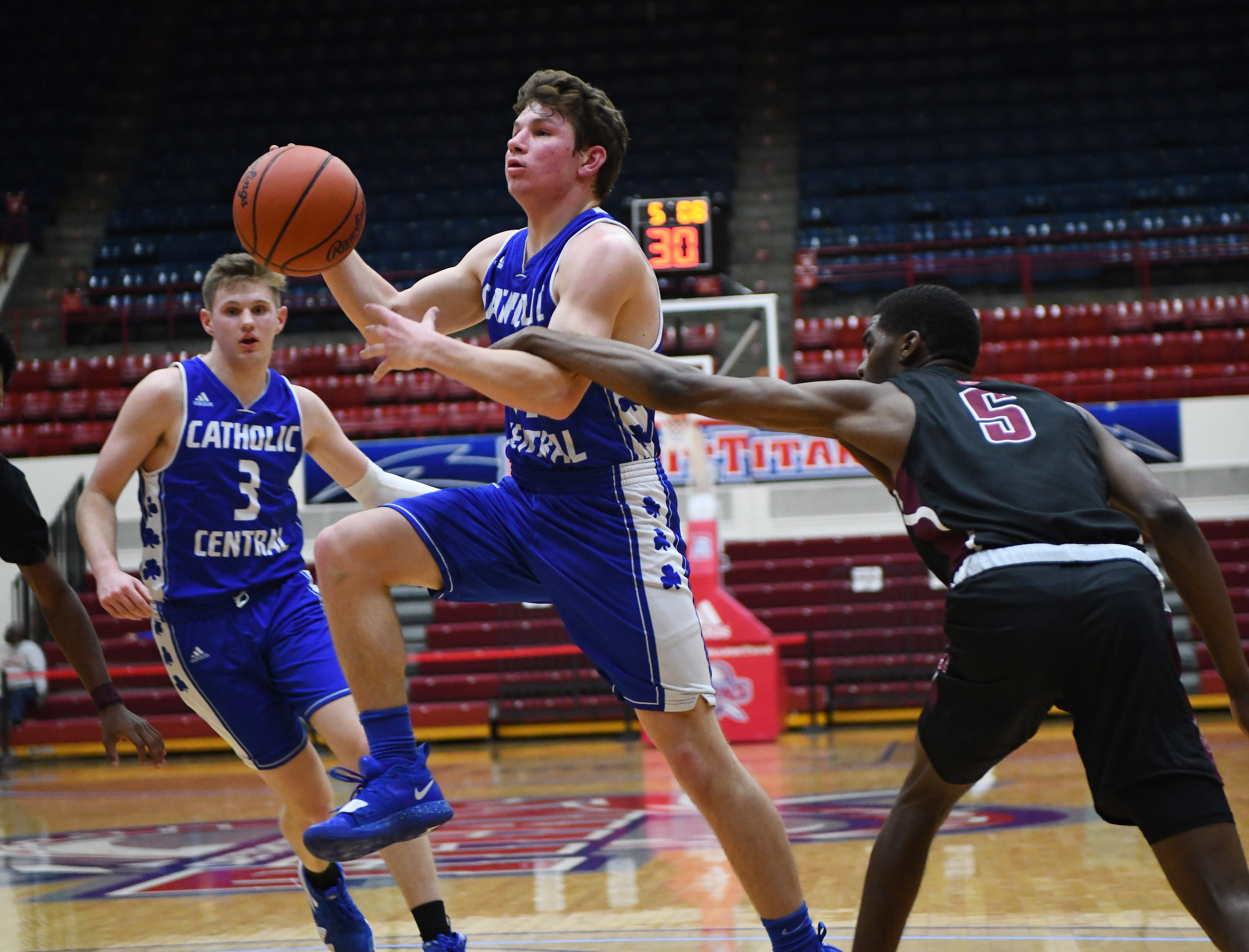 Catholic Central's Keegan Koehler gets fouled by Renaissance's Kaylein Marzetter as he drives to the basket in the first half of the consolation game.