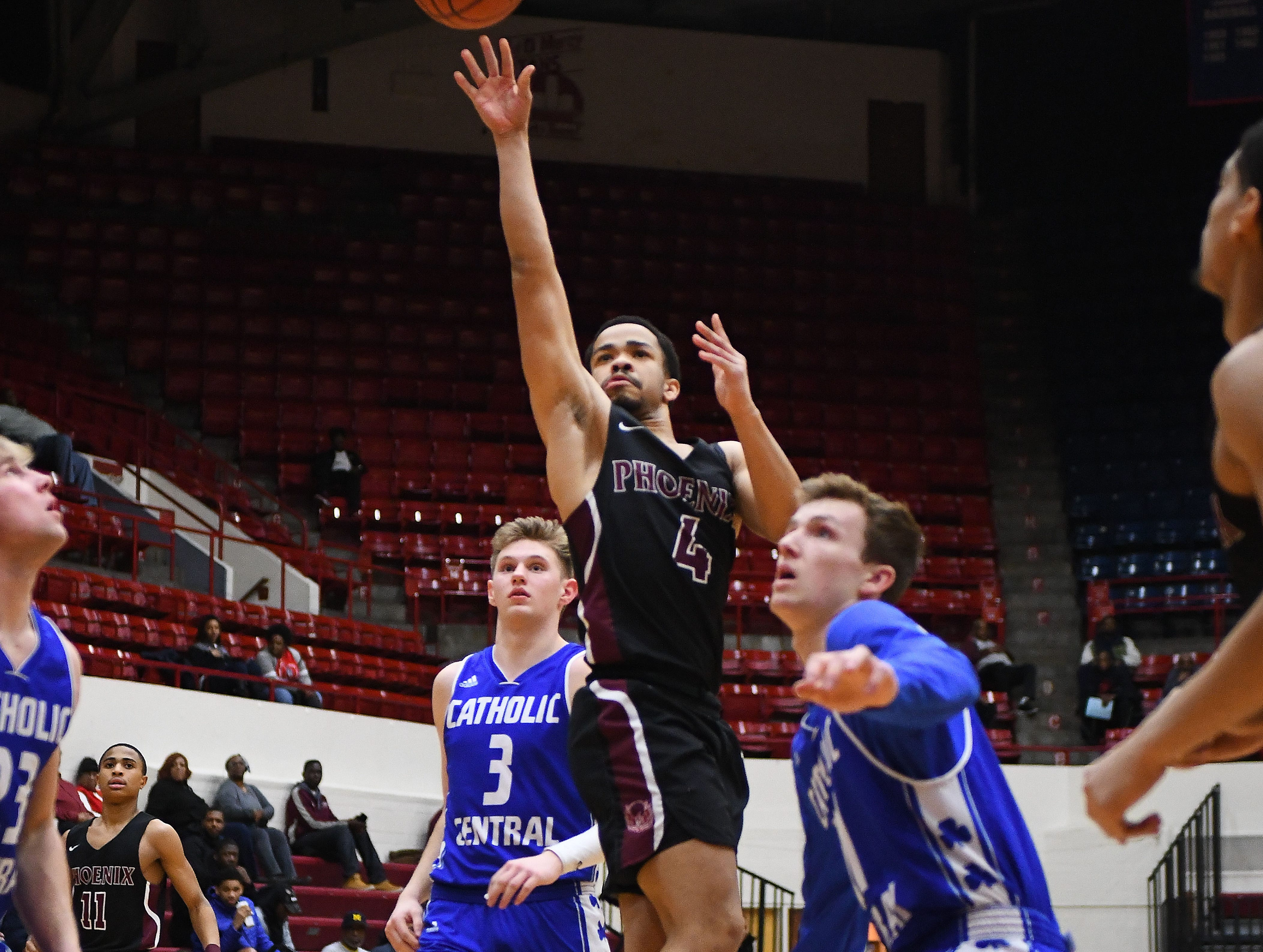Renaissance's Angelo Robertson splits the defense of Catholic Central's Davis Lukomski and Justin Rukat and puts up a shot in the first half of the Operation Friendship consolation game between Renaissance and Catholic Central at Calihan Hall on the campus of the University of Detroit Mercy in Detroit, Michigan on February 22, 2019.