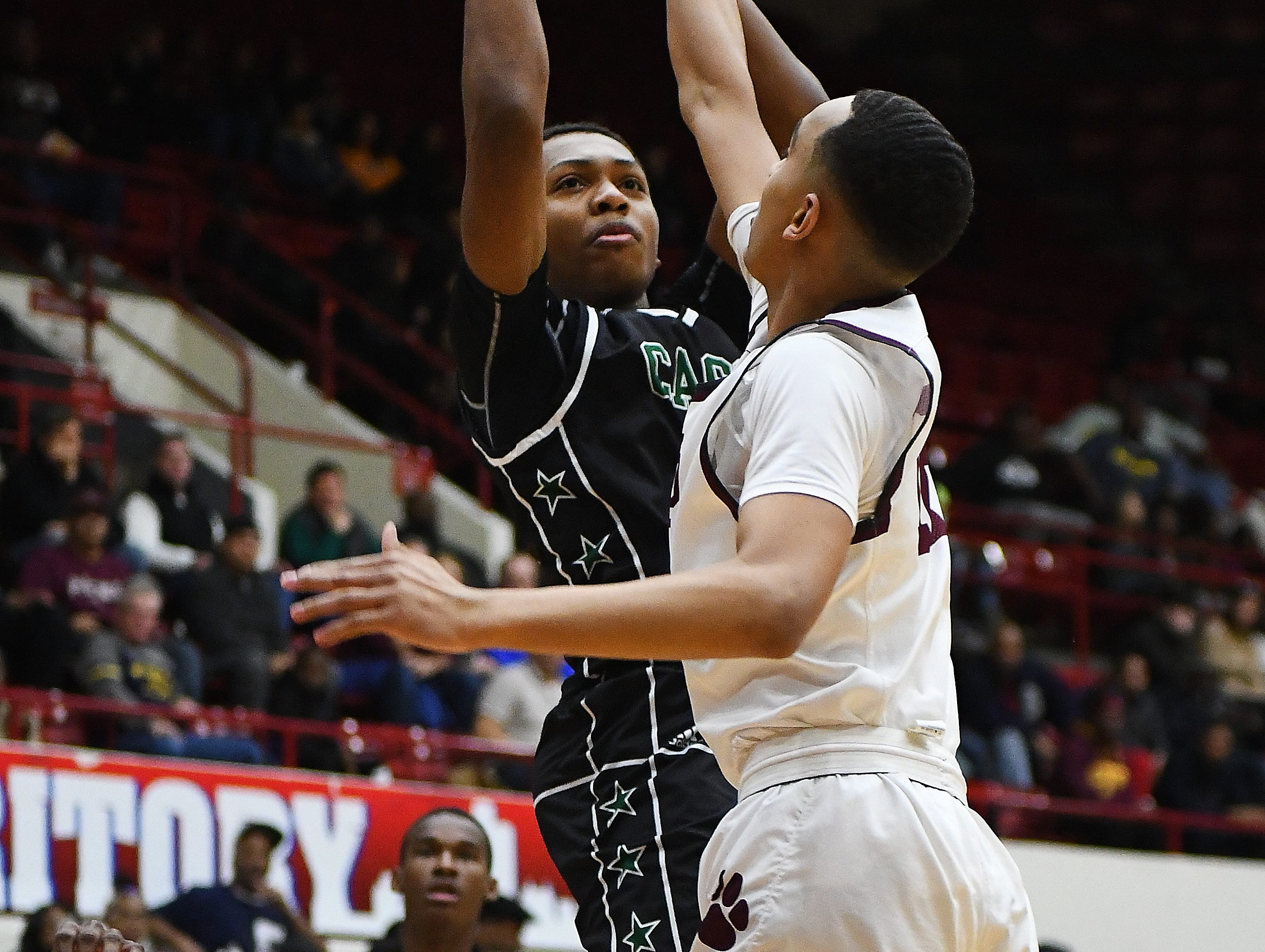 Cass Tech's Isaiah Sanders puts up a shot over U of D Jesuit's J. T. Morgan in the first half of the championship game.