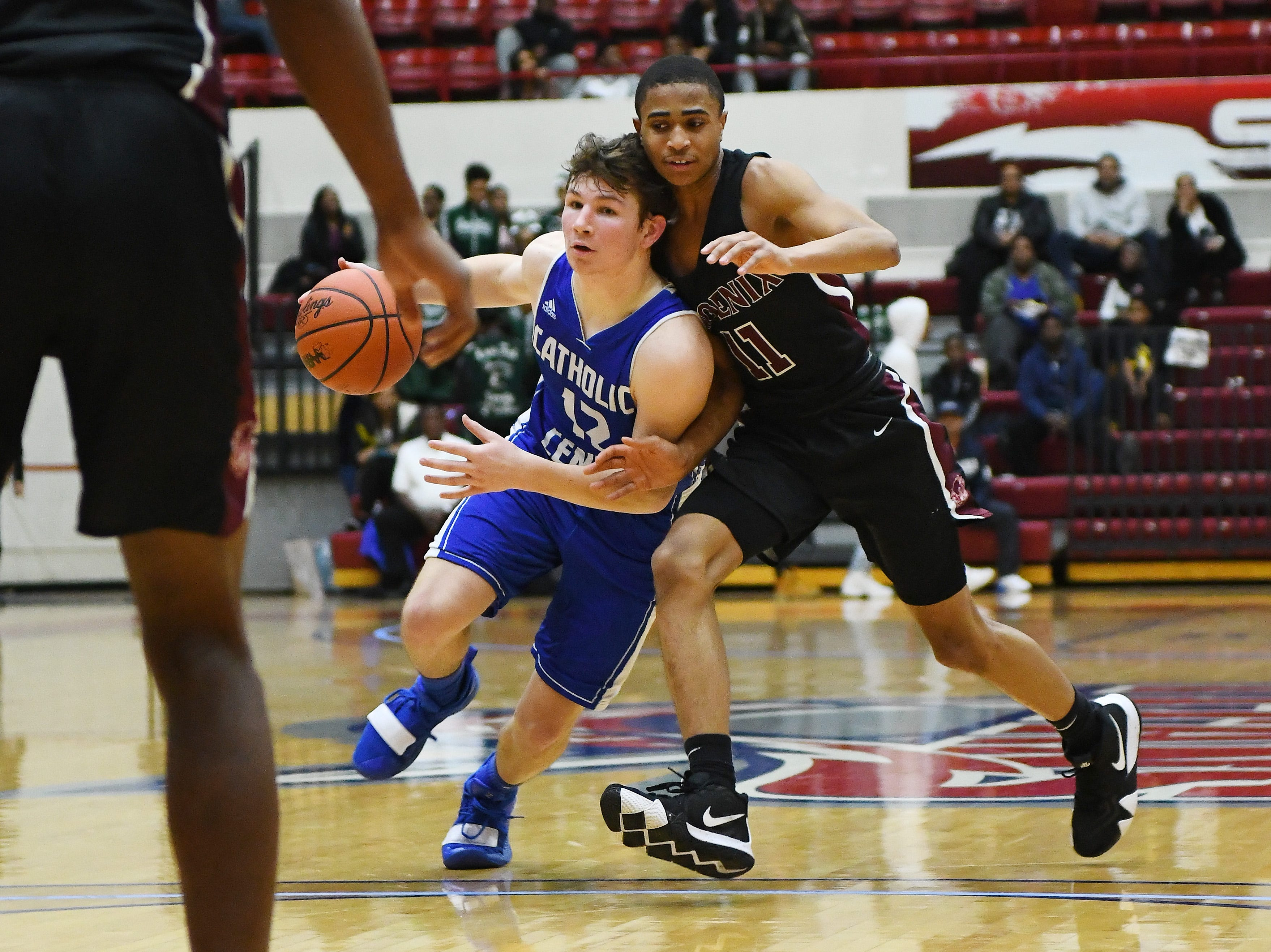 Catholic Central's Keegan Koehler brings the ball up court against Renaissance's Juwan Maxey in the second half of the consolation game.