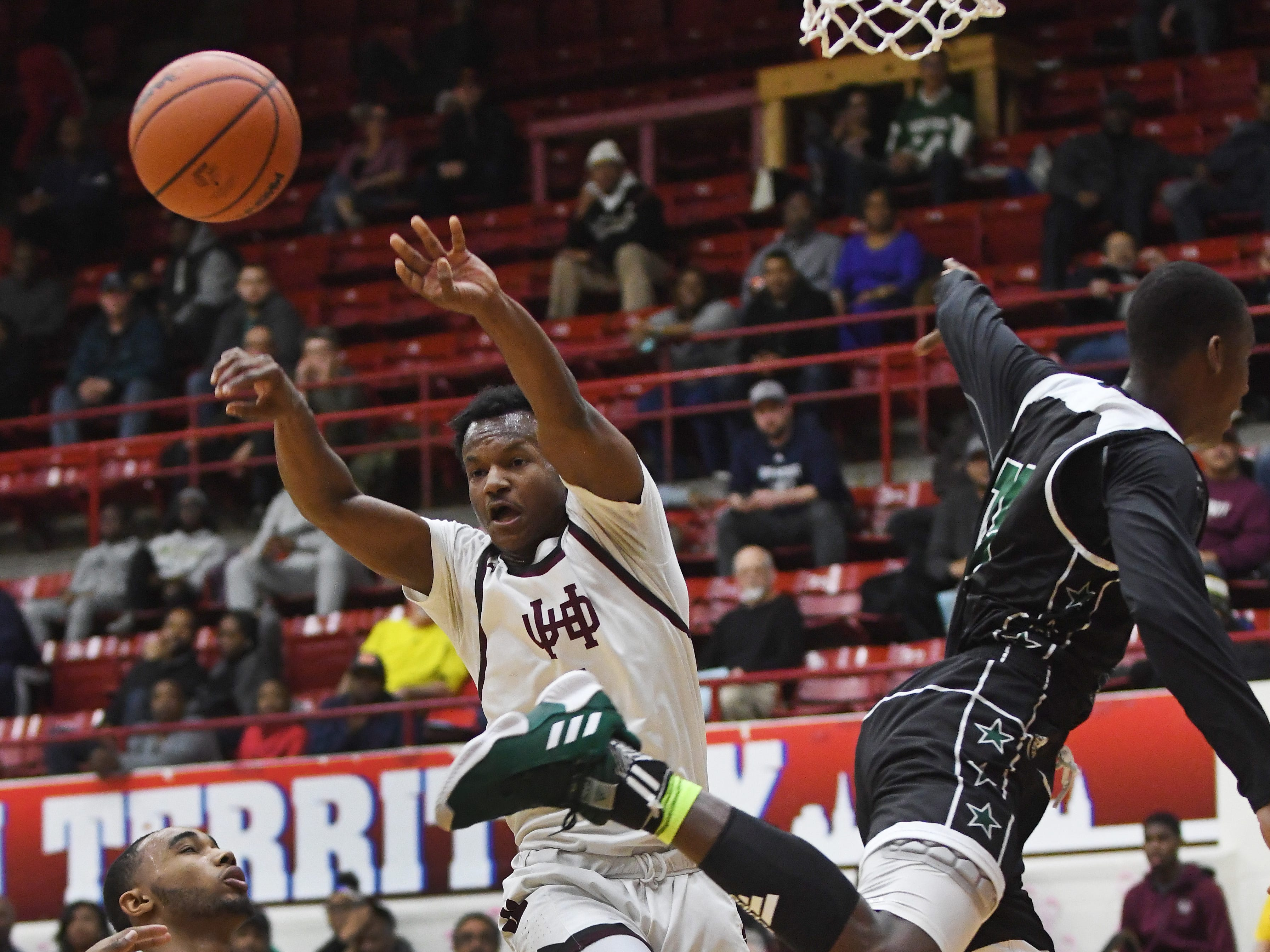 U of D Jesuit's Julian Dozier passes out of pressure from Cass Tech's Joshua Harris under the basket in the first half.