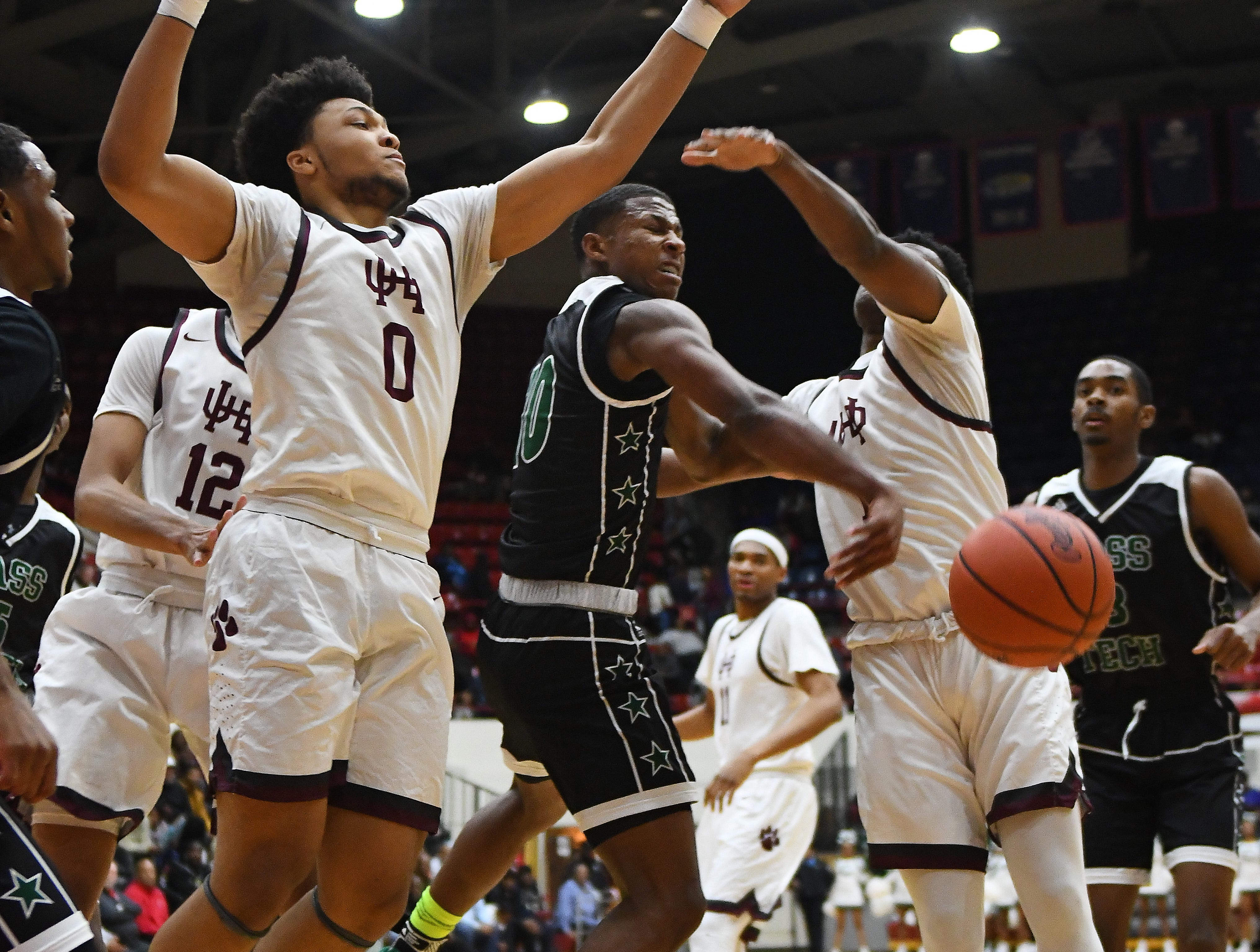 Cass Tech's Michael Washington Hills pass out of pressure by  U of D Jesuit's Daniel Friday and Julian Dozier in the first half of the championship game.
