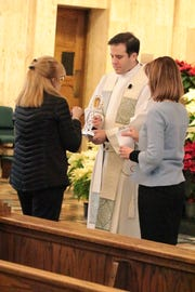 A parishioner venerated the Casey relic last month with the Rev. Matthew Hood, associate pastor, and Jodi Ann Micallef, evangelization coordinator, at Church of the Divine Child in Dearborn.