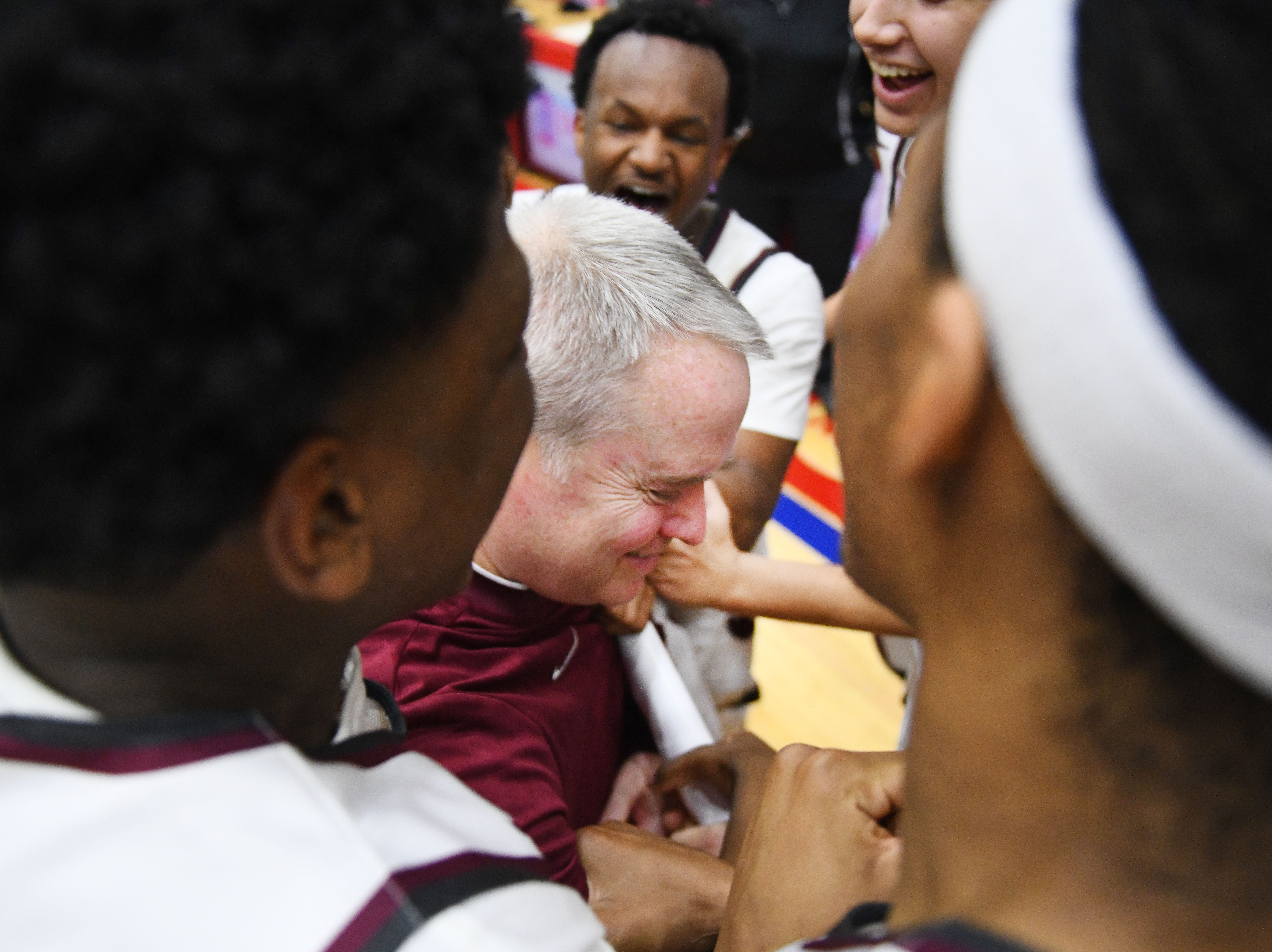 U of D Jesuit coach Pat Donnelly is mobbed by his players after the victory which was Donnellly's 200th win.