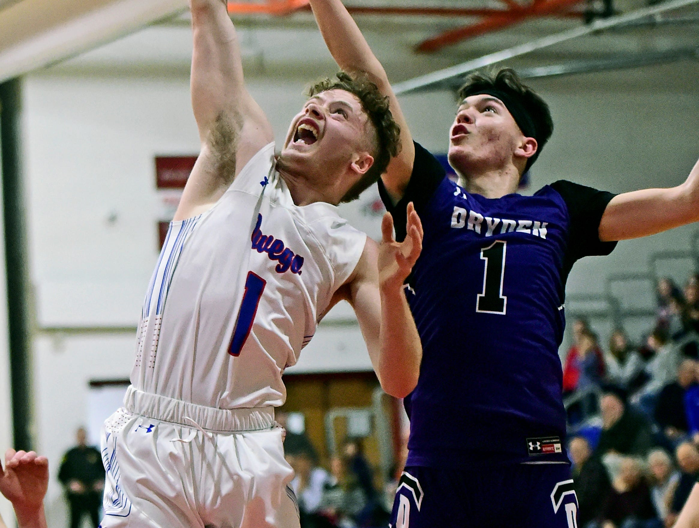 Owego's Christian Sage (1) looks to gain control of a rebound over Dryden's Michael Yuz'vak (1) during Friday's Section 4 Class B boys basketball quarterfinal, Dryden at Owego Free Academy, February 22, 2019.