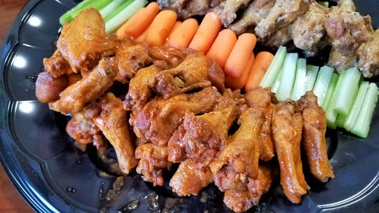 A platter of buffalo and garlic parm wings from Wingz & Thingz, with carrots, celery sticks and ranch dip.