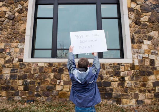 Evansville resident Steve Gray holds a protest sign outside a window at North Park Library during the EVPL's Drag Queen Story Hour Saturday, Feb. 23, 2019.