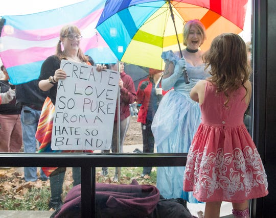 Charlotte Perkins, 3, looks out a window at LGBTQ supporters Erica fahrlender, left, and Loren Harrison dressed as Cinderella during EVPL's Drag Queen Story Hour at North Park Library Saturday, Feb. 22, 2019.