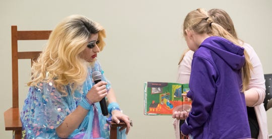 EVPL's Drag Queen Story Hour performer Florintine Dawn ask a volunteer to point out the cow jumping over the moon in the book Goodnight Moon Saturday, Feb. 22, 2019.