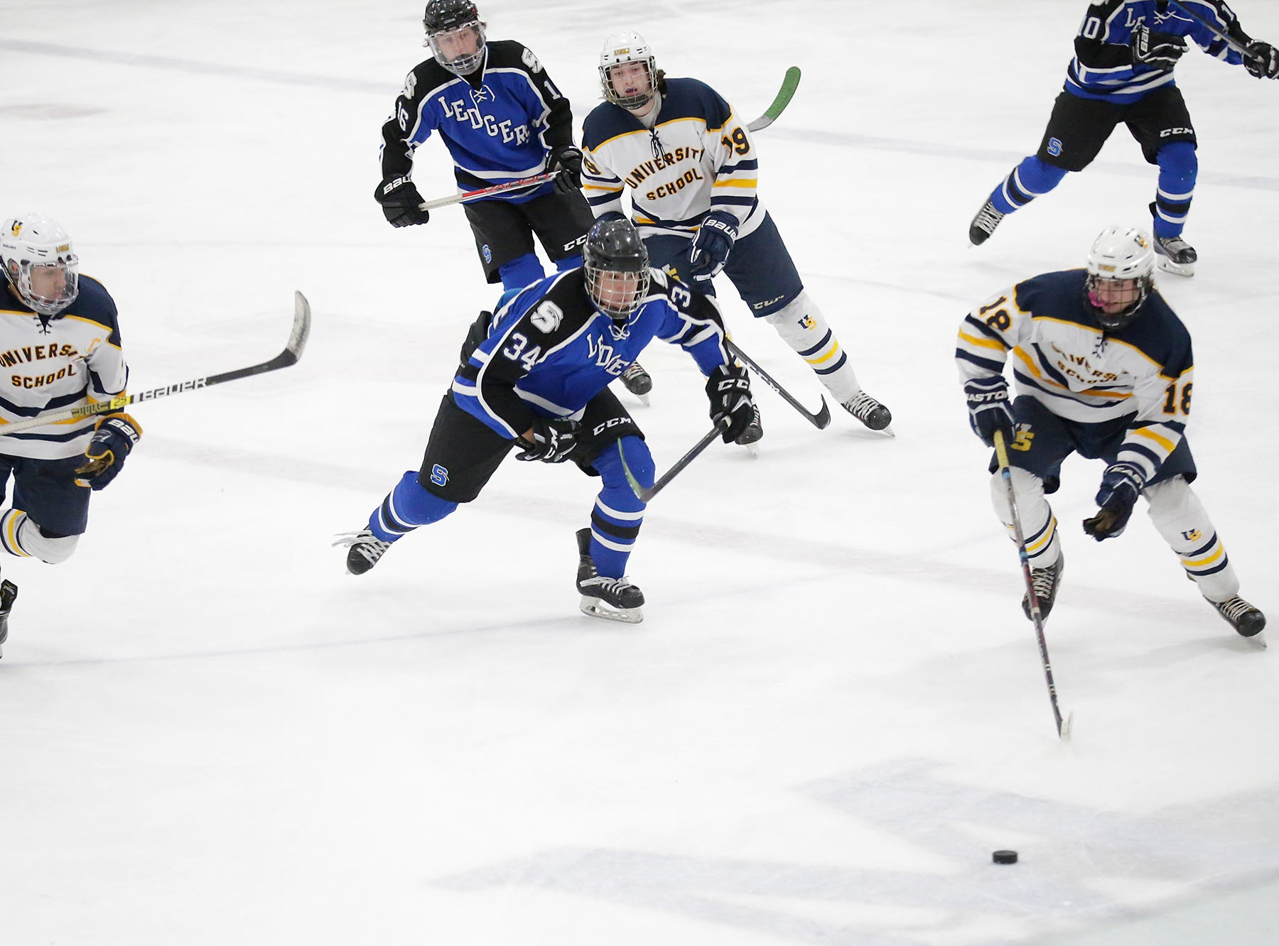 St. Mary's Springs boys co-op hockey's Cade Sabel (34) and University School of Milwaukee's Ethan Ford (10) and TJ Fenton (18) race to get the puck Friday, February 22, 2019 during their WIAA sectional final game in Fond du Lac. University School won the game 6-1 and will advance to state. Doug Raflik/USA TODAY NETWORK-Wisconsin