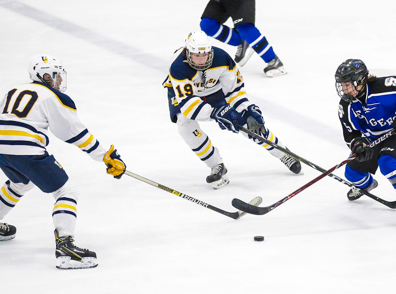 St. Mary's Springs boys co-op hockey's Brady Welsch (5) tries to keep the puck away from University School of Milwaukee's Ethan Ford (10) and Carson Mogush (19) Friday, February 22, 2019 during their WIAA sectional final game in Fond du Lac. University School won the game 6-1 and will advance to state. Doug Raflik/USA TODAY NETWORK-Wisconsin