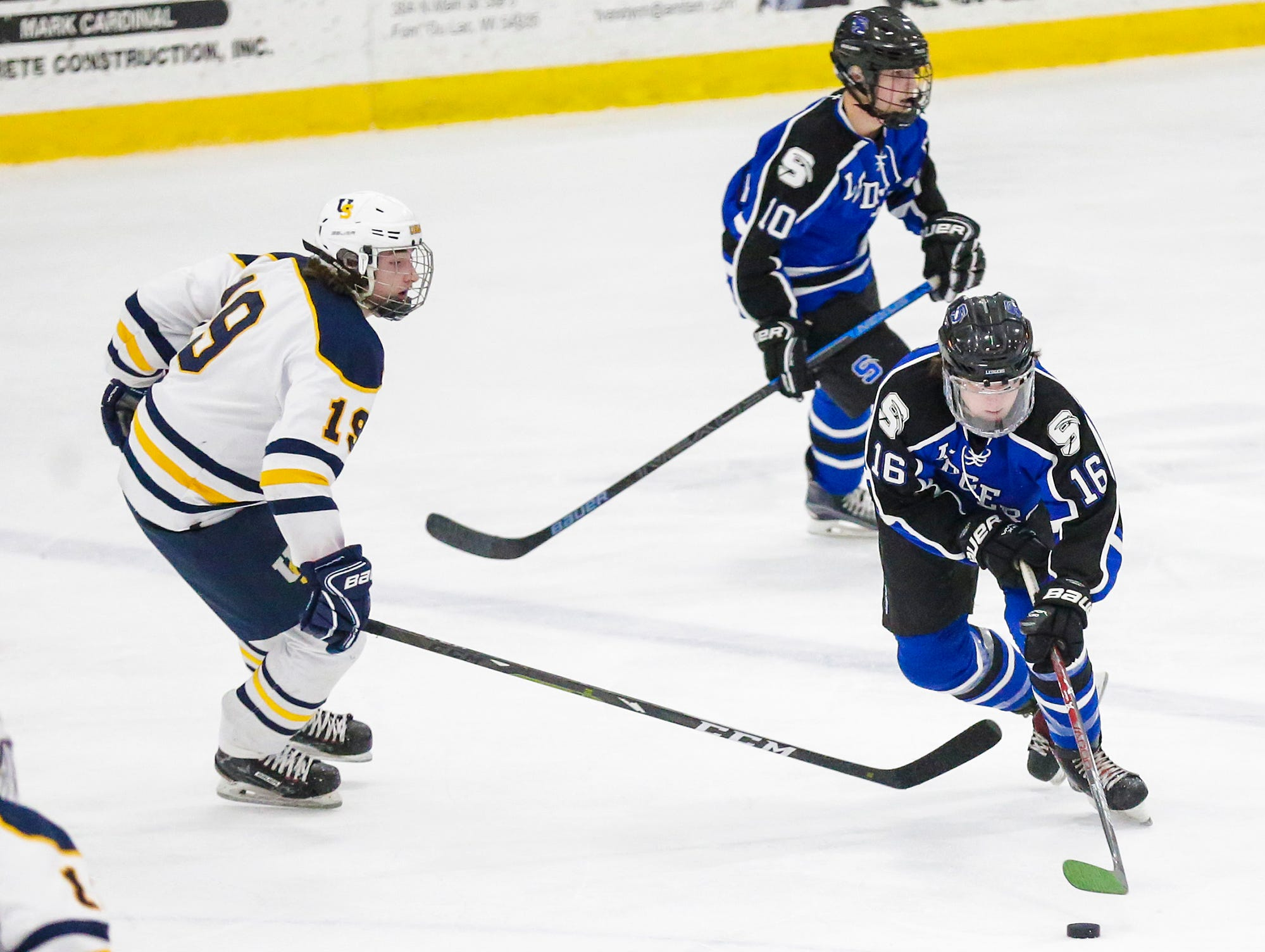 St. Mary's Springs boys co-op hockey's Caleb Schaefer (16) moves the puck around University School of Milwaukee's Carson Mogush (19) Friday, February 22, 2019 during their WIAA sectional final game in Fond du Lac. University School won the game 6-1 and will advance to state. Doug Raflik/USA TODAY NETWORK-Wisconsin