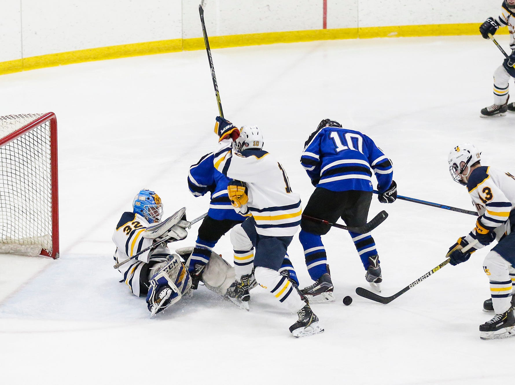 St. Mary's Springs boys co-op hockey's Zach Welsch (8) and Dayne Deanovich (10) fight for the puck with University School of Milwaukee's Patrick Kelly (32), Ethan Ford (10) and Robby Newton (13) Friday, February 22, 2019 during their WIAA sectional final game in Fond du Lac. University School won the game 6-1 and will advance to state. Doug Raflik/USA TODAY NETWORK-Wisconsin
