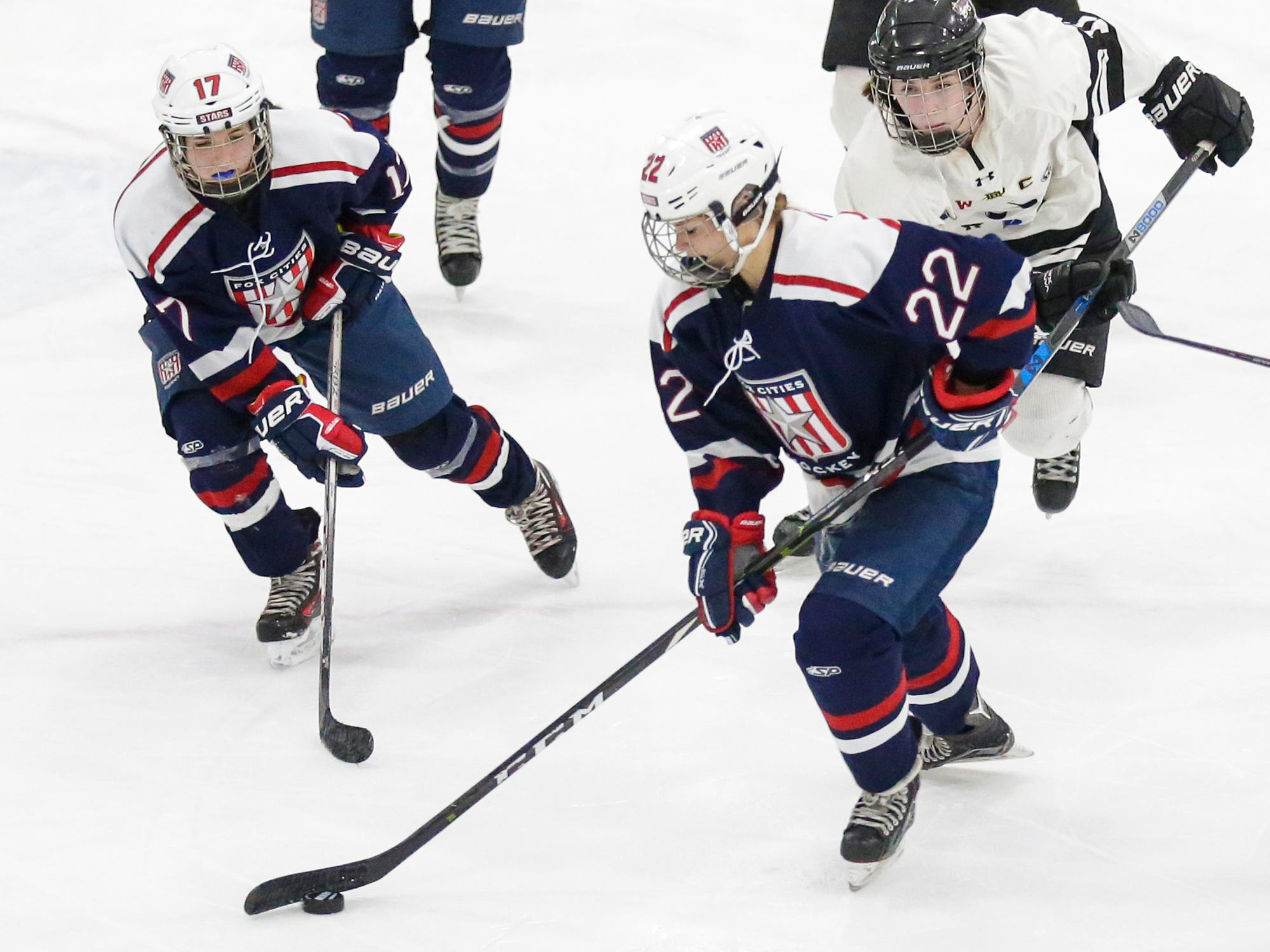 Fox Cities Stars girls hockey's Riley Maulick (22) moves the puck with Morgan Treml (17) and Beaver Dam Alliance's Morgan Brown (11) right behind Friday, February 22, 2019 during their WIAA sectional final game in Fond du Lac. Fox Cities Stars won the game 5-2 and will advance to state. Doug Raflik/USA TODAY NETWORK-Wisconsin