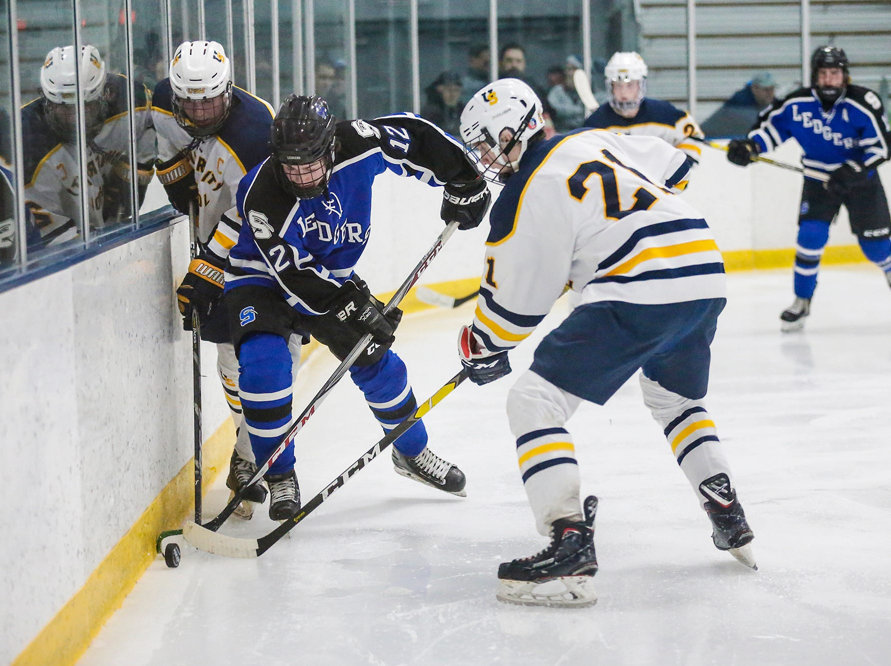 St. Mary's Springs boys co-op hockey's Mitchell Huettl (12) battles for the puck with University School of Milwaukee's Blake Carey (25) and Casey Roepke (21) Friday, February 22, 2019 during their WIAA sectional final game in Fond du Lac. University School won the game 6-1 and will advance to state. Doug Raflik/USA TODAY NETWORK-Wisconsin