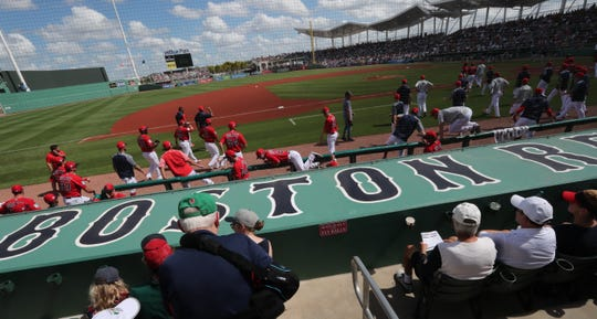 Boston Red Sox players jump the dugout fence to take the field for the start of the game. Boston Red Sox were victorious over the New York Yankees in front of packed house in their spring training opener at Jet Blue Park, Fort Myers, Florida. February 23, 2019.