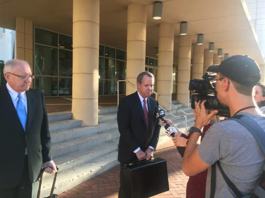 Attorney John Fitzgibbons, center, speaks with reporters after his clients, Robert Gow, left and his wife, Kay were convicted on all counts in connection with the plundering of Lee County grant funds.