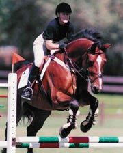 Rep. Nancy Ballance took up competitive horse jumping as a hobby. Pictured above, Ballance competes in 2004 with her German horse, Lavall, a Holsteiner.